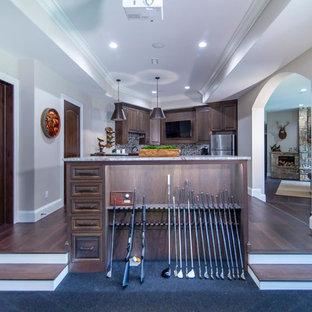 Cette photo montre un grand sous-sol donnant sur l'extérieur avec un mur gris, un sol en bois brun, une cheminée standard, un manteau de cheminée en pierre et un sol marron.