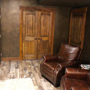 Idée de décoration pour un sous-sol craftsman enterré et de taille moyenne avec un mur noir, un sol en bois brun, une cheminée standard, un manteau de cheminée en pierre et un sol gris.