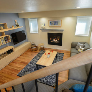 Example of a small minimalist medium tone wood floor basement design in Denver with yellow walls and a standard fireplace