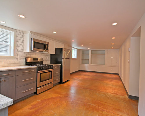 example of a minimalist basement design in seattle with orange floors - Basement Kitchen Designs