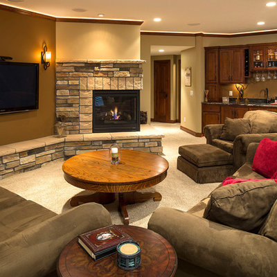 Elegant underground carpeted and beige floor basement photo in Minneapolis with beige walls, a corner fireplace and a stone fireplace