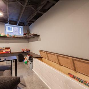 Cette photo montre un grand sous-sol chic semi-enterré avec un mur bleu, béton au sol, aucune cheminée et un sol bleu.