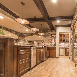 Inspiration for a large rustic underground ceramic floor and gray floor basement remodel in Detroit with beige walls, a standard fireplace and a stone fireplace
