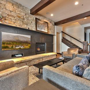 Inspiration pour un sous-sol chalet avec un mur blanc, un sol en bois brun, une cheminée standard, un manteau de cheminée en métal et un sol marron.