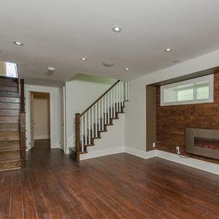 Réalisation d'un sous-sol chalet semi-enterré et de taille moyenne avec un mur blanc, un sol en bois foncé, une cheminée ribbon, un manteau de cheminée en métal et un sol marron.