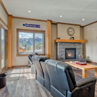 Idées déco pour un sous-sol montagne donnant sur l'extérieur et de taille moyenne avec salle de jeu, un mur beige, un sol en bois brun, une cheminée standard, un manteau de cheminée en pierre de parement et un sol marron.
