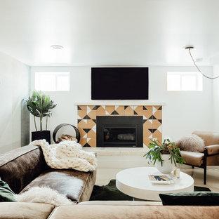 Cette image montre un sous-sol bohème semi-enterré et de taille moyenne avec un mur multicolore, béton au sol, une cheminée standard, un manteau de cheminée en carrelage et un sol gris.