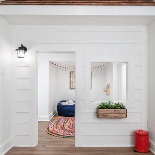 Cette photo montre un très grand sous-sol craftsman semi-enterré avec un mur blanc, un sol en bois brun, aucune cheminée et un sol beige.