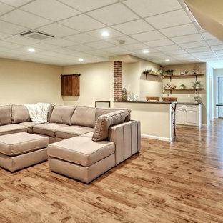 Inspiration pour un grand sous-sol urbain avec un mur beige et sol en stratifié.