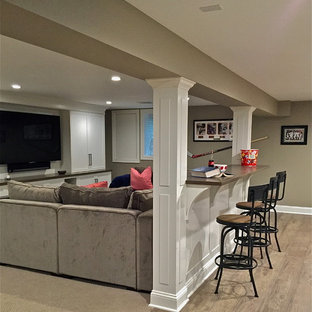 Large transitional underground laminate floor and gray floor basement photo in New York with beige walls and no fireplace