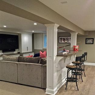 Diseño de sótano en el subsuelo tradicional renovado, grande, sin chimenea, con paredes beige, suelo laminado y suelo gris