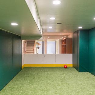 Réalisation d'un grand sous-sol minimaliste enterré avec un mur vert, moquette, aucune cheminée et un sol vert.