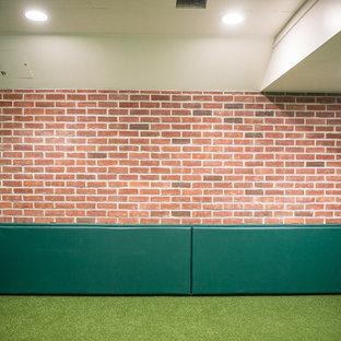 Aménagement d'un grand sous-sol moderne enterré avec un mur vert, moquette, aucune cheminée et un sol vert.