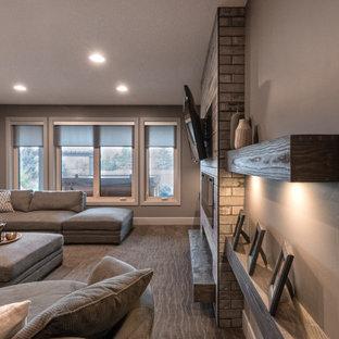 Cette photo montre un grand sous-sol montagne donnant sur l'extérieur avec salle de jeu, un mur gris, moquette, une cheminée standard, un manteau de cheminée en brique, un sol marron, un plafond en poutres apparentes et du lambris.