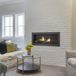 Exemple d'un sous-sol chic de taille moyenne et semi-enterré avec un mur gris, moquette, une cheminée ribbon et un manteau de cheminée en brique.