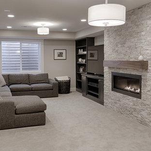Aménagement d'un sous-sol contemporain de taille moyenne et enterré avec un mur gris, moquette, une cheminée standard et un manteau de cheminée en pierre.