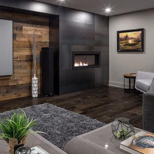 Aménagement d'un sous-sol contemporain avec un sol en bois foncé, un manteau de cheminée en métal et un sol marron.