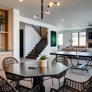 Idée de décoration pour un grand sous-sol design avec salle de jeu, un mur blanc, moquette, une cheminée standard, un manteau de cheminée en bois et un sol gris.