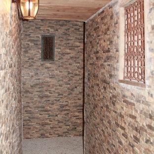 Idées déco pour un grand sous-sol méditerranéen donnant sur l'extérieur avec un mur beige et un sol en travertin.