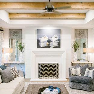 Exemple d'un grand sous-sol chic donnant sur l'extérieur avec un mur blanc, un sol en bois clair, une cheminée standard, un manteau de cheminée en béton et un sol marron.
