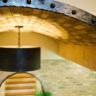 Idée de décoration pour un grand sous-sol tradition donnant sur l'extérieur avec un mur blanc, un sol en bois clair, une cheminée standard, un manteau de cheminée en béton et un sol marron.