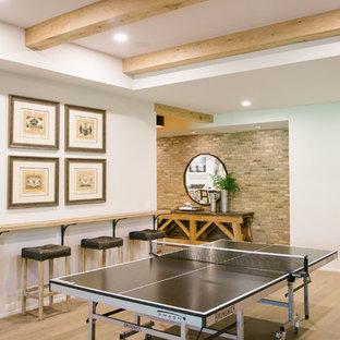 Cette image montre un grand sous-sol traditionnel donnant sur l'extérieur avec un mur blanc, un sol en bois clair, une cheminée standard, un manteau de cheminée en béton et un sol marron.