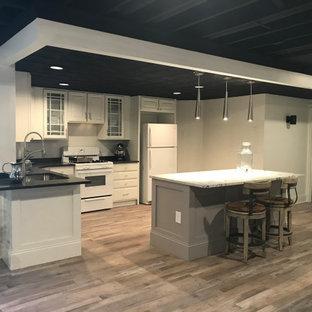 Idée de décoration pour un grand sous-sol minimaliste donnant sur l'extérieur avec un mur blanc, un sol en vinyl, une cheminée standard, un manteau de cheminée en brique et un sol gris.