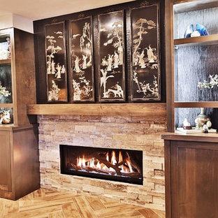 Esempio di una taverna etnica di medie dimensioni con sbocco, pareti bianche, pavimento in gres porcellanato, camino classico, cornice del camino in pietra e pavimento marrone