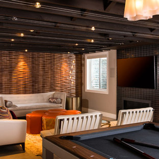 Mid-sized midcentury fully buried basement in Other with concrete floors, a ribbon fireplace, a tile fireplace surround, beige walls and beige floor.
