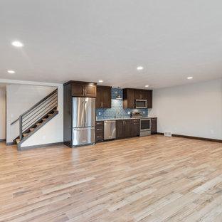 Exemple d'un grand sous-sol chic donnant sur l'extérieur avec salle de jeu, un mur blanc, un sol en carrelage de céramique, aucune cheminée et un sol marron.