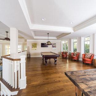 Idée de décoration pour un grand sous-sol tradition donnant sur l'extérieur avec salle de jeu, un mur beige, un sol en bois brun, aucune cheminée, un sol marron et un plafond décaissé.