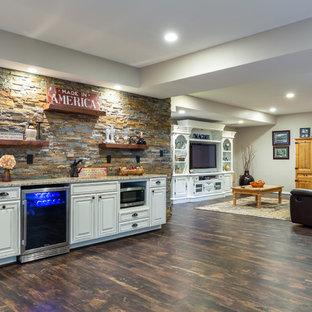 Cette image montre un grand sous-sol traditionnel enterré avec un mur beige, un sol en vinyl, aucune cheminée et un sol marron.