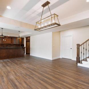 Exemple d'un sous-sol montagne donnant sur l'extérieur avec un bar de salon, un sol en bois brun, un sol marron et un plafond décaissé.