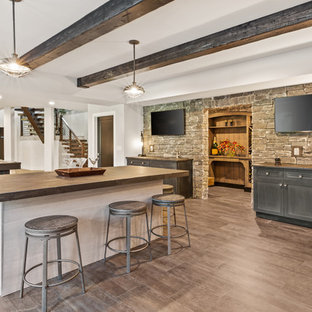 Inspiration for a large country walk-out vinyl floor and brown floor basement remodel in Cincinnati with white walls, a standard fireplace and a stone fireplace