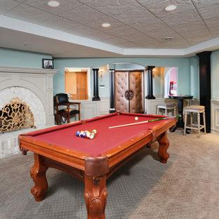 Cette image montre un grand sous-sol traditionnel enterré avec salle de jeu, un mur bleu, moquette, une cheminée d'angle, un manteau de cheminée en brique, un sol beige, un plafond décaissé et du lambris.