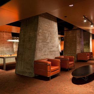 Idee per un'ampia taverna industriale interrata con pareti arancioni, moquette, nessun camino e pavimento arancione