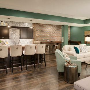 This is an example of a large transitional walk-out basement in Philadelphia with green walls, dark hardwood floors, no fireplace and brown floor.