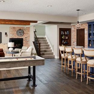 Inspiration pour un sous-sol urbain de taille moyenne avec un mur gris, un sol en vinyl, une cheminée d'angle et un manteau de cheminée en brique.