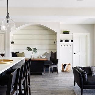 Réalisation d'un grand sous-sol tradition donnant sur l'extérieur avec un mur gris, un sol en vinyl et un sol gris.