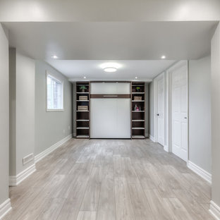 Inspiration for a small coastal walk-out laminate floor basement remodel in Toronto with white walls