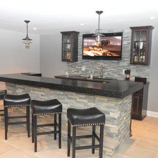 Idée de décoration pour un sous-sol tradition donnant sur l'extérieur et de taille moyenne avec un mur gris, un sol en bois brun, une cheminée standard, un manteau de cheminée en pierre et un sol marron.