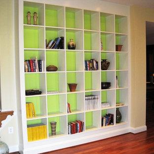 Réalisation d'un grand sous-sol minimaliste donnant sur l'extérieur avec un mur vert, un sol en bois clair et aucune cheminée.