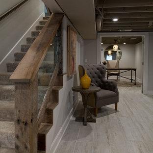 Inspiration pour un grand sous-sol rustique enterré avec un mur gris, un sol en bois clair et un sol gris.