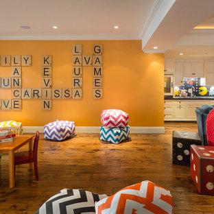 Ispirazione per una taverna classica con sbocco, pavimento in legno massello medio, nessun camino e pareti arancioni