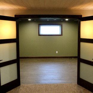 Aménagement d'un grand sous-sol classique enterré avec un mur beige, moquette, une cheminée standard et un manteau de cheminée en pierre.