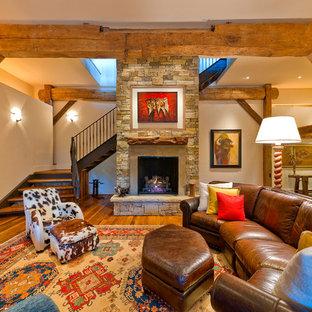 Idées déco pour un sous-sol classique enterré avec un manteau de cheminée en pierre, une cheminée standard, un sol en bois brun, un mur beige et un sol orange.