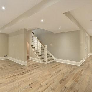 Inredning av en klassisk mellanstor källare, med grå väggar och ljust trägolv
