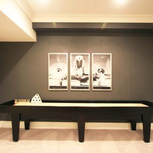 Réalisation d'un très grand sous-sol design semi-enterré avec un mur gris, moquette, une cheminée standard et un manteau de cheminée en pierre.