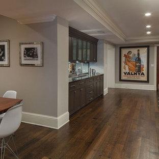 Cette photo montre un grand sous-sol chic semi-enterré avec un mur gris, un sol en bois foncé et un sol marron.