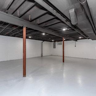 Cette photo montre un très grand sous-sol chic semi-enterré avec un mur blanc, béton au sol, aucune cheminée et un sol gris.